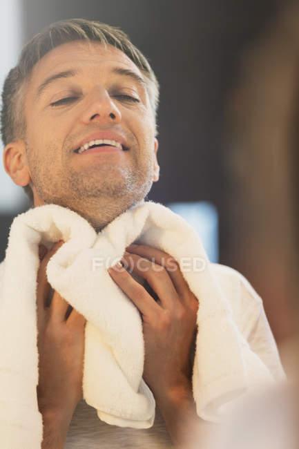 Людина, витираючи шию в дзеркало — стокове фото