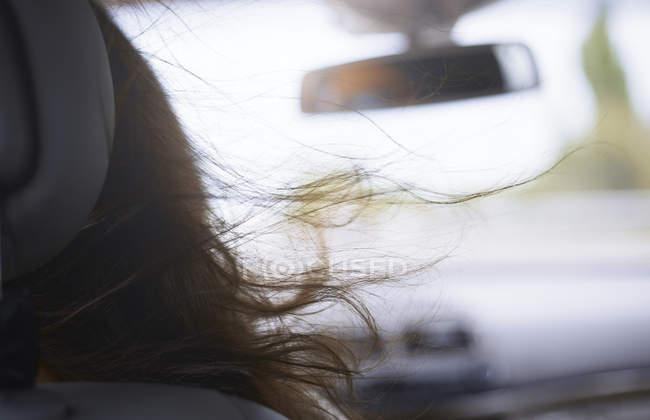 Mujer cabello soplando en coche - foto de stock
