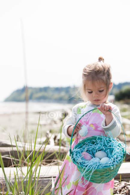 Дівчина збір великодні яйця в кошику на пляжі — стокове фото