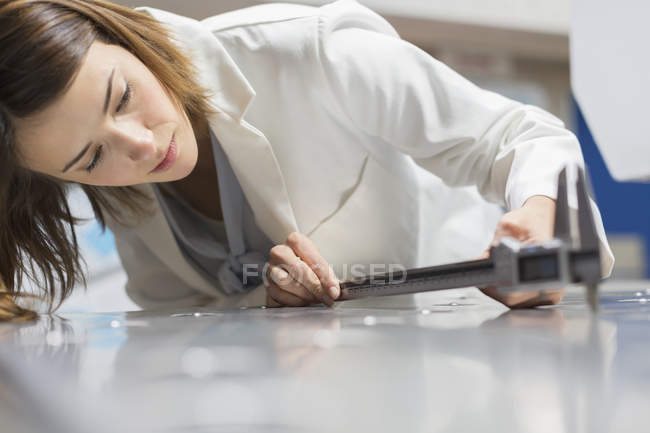 Engineer with calipers measuring sheet metal in steel factory — Stock Photo