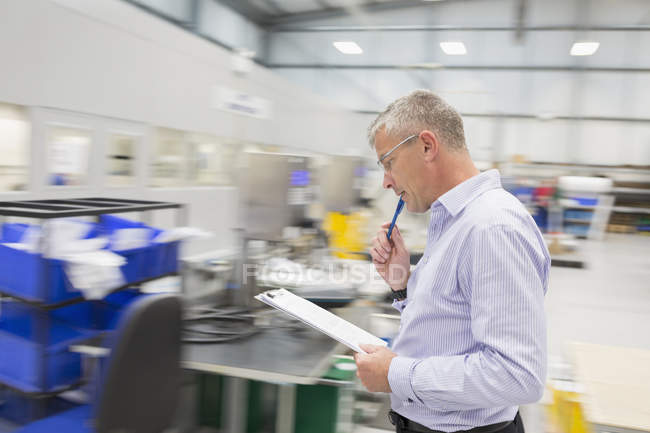 Manager with clipboard walking in steel factory — Stock Photo