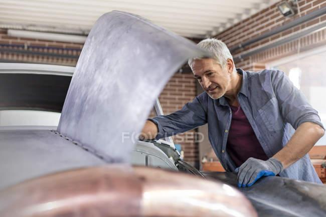 Meccanico guardando sotto il cofano dell'automobile in officina di riparazione auto — Foto stock