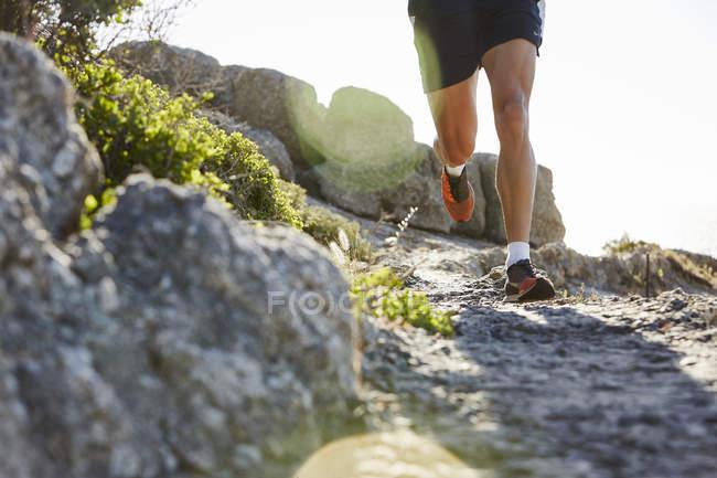 Бегущий по скалистой тропе мужчина — стоковое фото