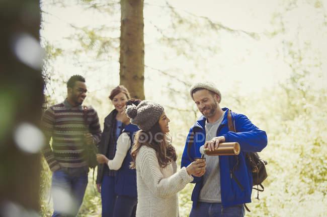 Усміхаючись друзів походи розливу кави з ізольованих напій контейнера в лісі — стокове фото