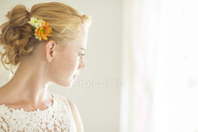 Portrait of young bride looking out of window — Stock Photo