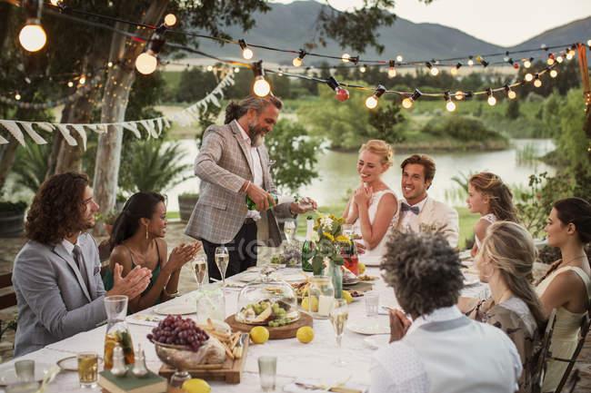 Шафер наливает шампанское на флейты во время свадебного приема в саду — стоковое фото