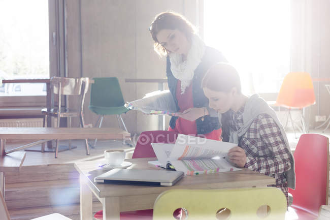Creative businesswomen reviewing document edits in sunny office — Stock Photo