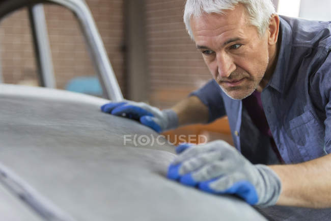 Focused mechanic examining automobile hood panel in auto repair shop — стоковое фото