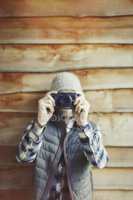 Portrait man using camera outside cabin — Stock Photo