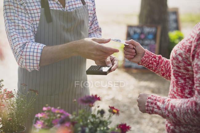 Женщина платит кредитной картой работнице питомника — стоковое фото