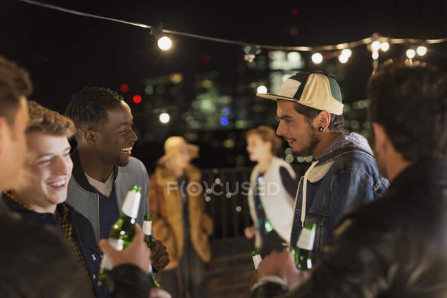 Giovani amici che parlano e bevono alla festa sul tetto — Foto stock