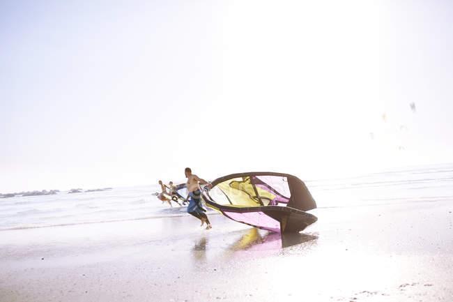 Man dragging kiteboarding equipment on beach — Stock Photo