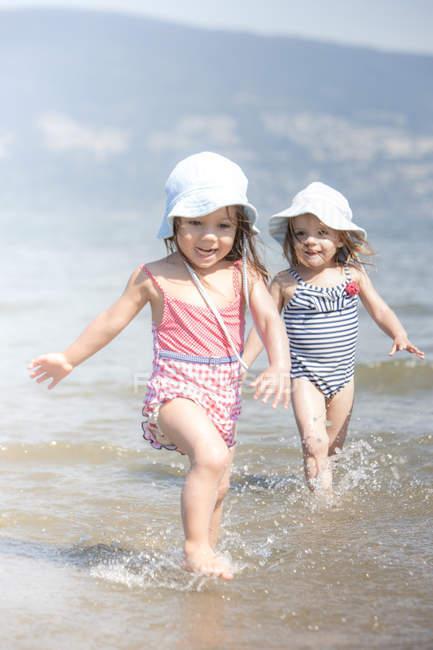 Girls wading in ocean — Stock Photo