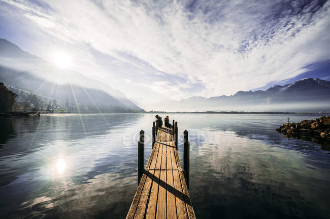 Couple at the edge of dock over sunny tranquil lake, Switzerland — Stock Photo