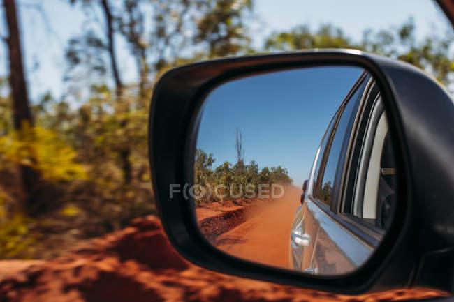 Rotem Lehm Staubwolke in Außenspiegel des Autos — Stockfoto