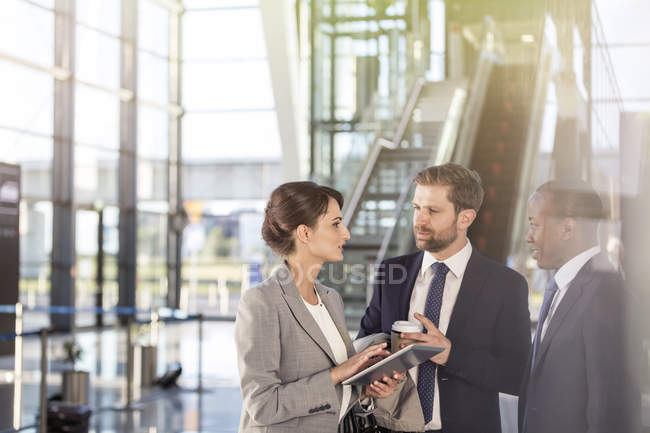 Business people with digital tablet talking in airport — Stock Photo