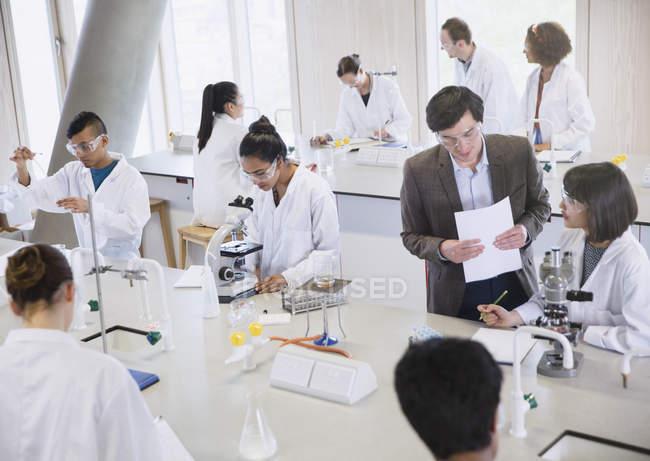 Professore di Scienze e studenti universitari utilizzando microscopi in aula laboratorio di Scienze — Foto stock