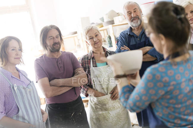 Teacher showing pottery bowl to mature students in studio — Stock Photo