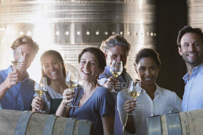 Портрет улыбающихся друзей дегустация вин в винном погребе — стоковое фото