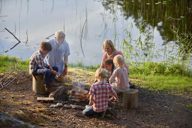 Grandparents and grandchildren enjoying campfire at lakeside — Stock Photo