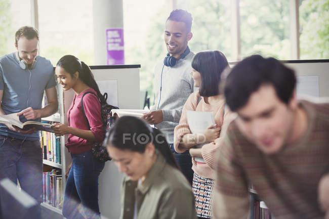 Studenti universitari che studiano nella libreria insieme — Foto stock