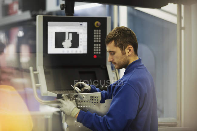 Worker inspecting steel at control panel in steel factory — Stock Photo
