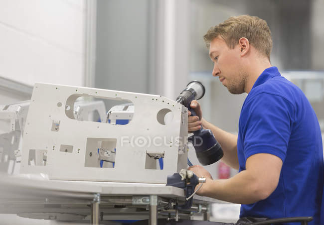 Worker using drill in steel factory — Stock Photo