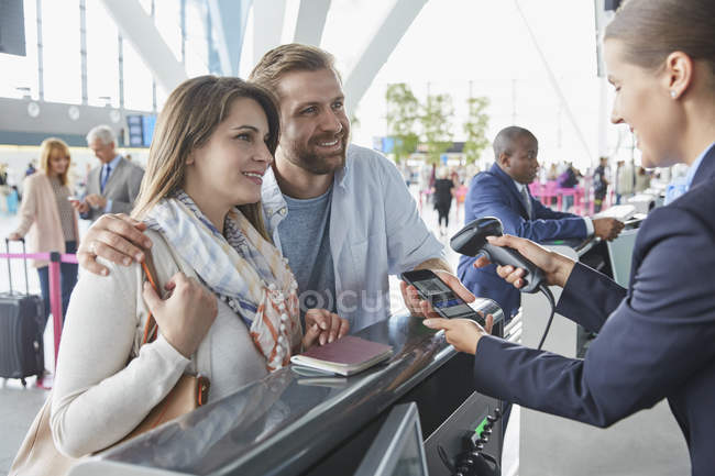 Customer service representative scanning smart phone QR code at airport check-in counter — Stock Photo