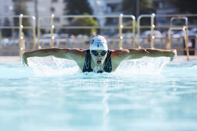 Athlète nageur masculin faisant course de papillon nageant dans la piscine — Photo de stock