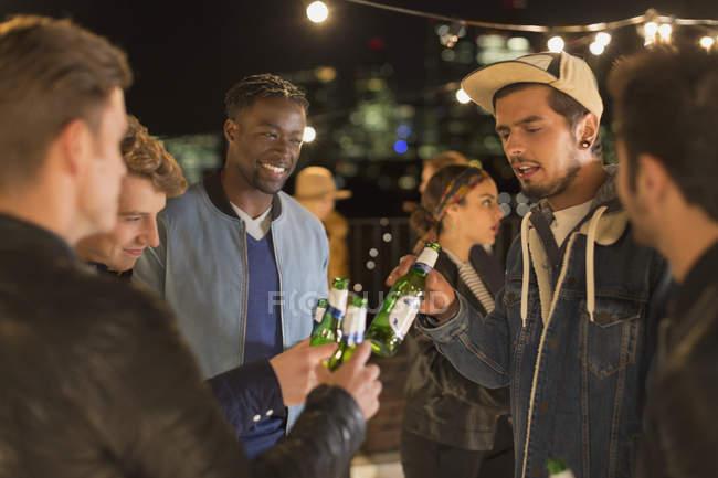 Jovens amigos adultos brindando garrafas de cerveja na festa no telhado — Fotografia de Stock