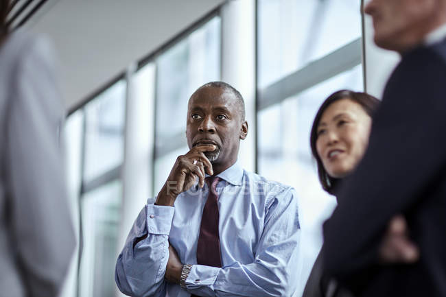 Attentive serious businessman listening to colleagues — Stock Photo
