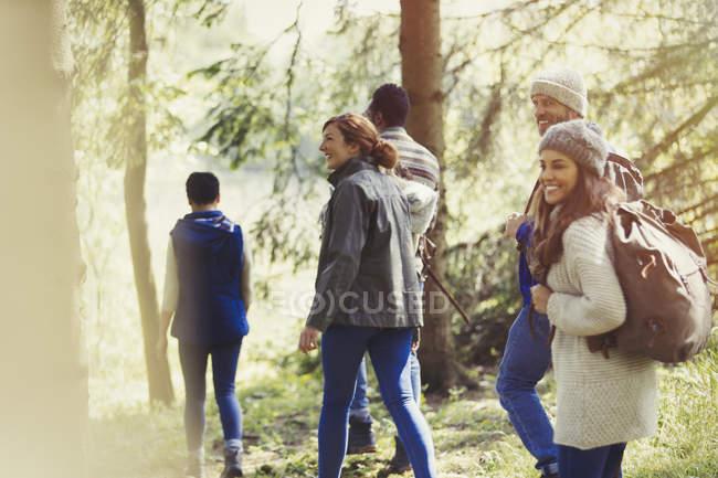 Улыбающиеся друзья, гуляющие по лесу — стоковое фото