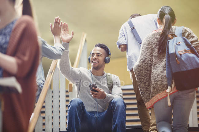 College students with headphones and mp3 player high-fiving in stairway — Stock Photo