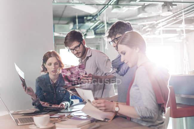 Creativi uomini d'affari che rivedono le prove in ufficio soleggiato — Foto stock