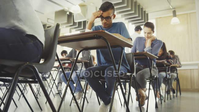 Studenti universitari che fanno test alla scrivania in classe — Foto stock