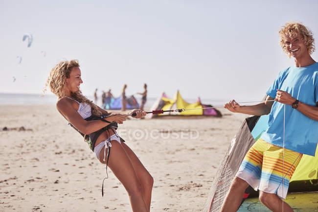 Playful couple preparing kiteboarding equipment on sunny beach — Stock Photo