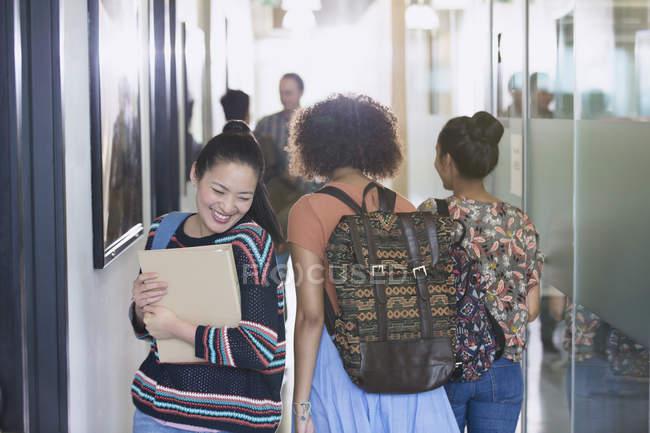 Smiling female college student walking in corridor — Stock Photo
