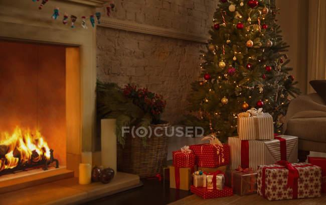 Рождественская елка и подарки возле камина в гостиной — стоковое фото