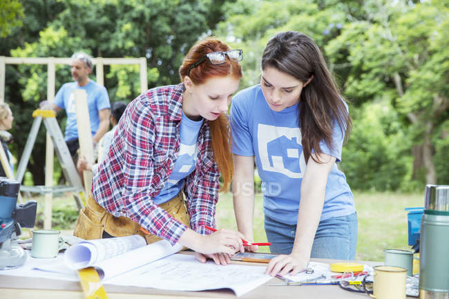Volunteers with digital tablet reviewing blueprints at construction site — Stock Photo