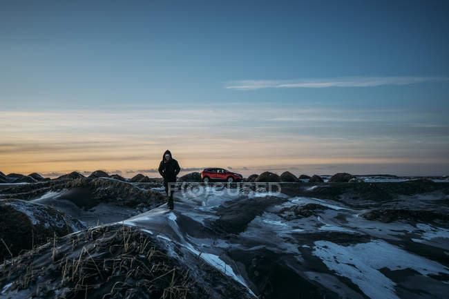 Uomo che cammina sul gelidi tumuli nel paesaggio remoto, Hofn, Islanda — Foto stock