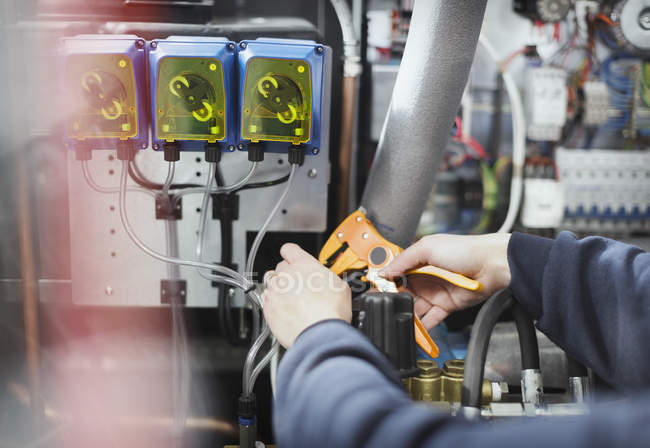 Worker using tool on machinery in steel factory — Stock Photo