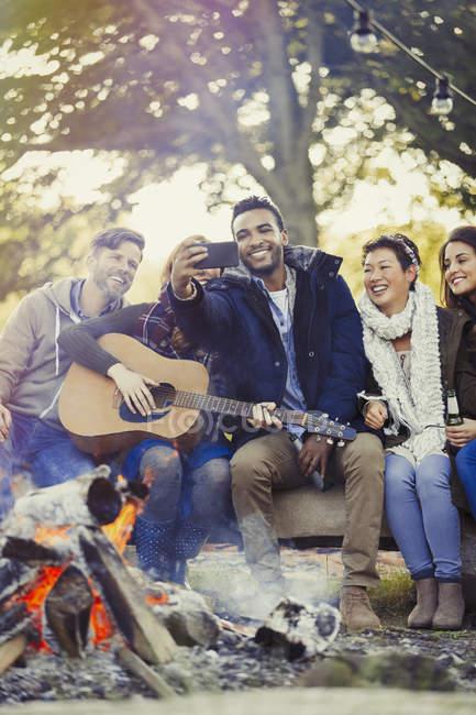 Amis avec guitare prenant selfie avec téléphone caméra au feu de camp — Photo de stock