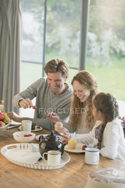 Семья есть кексы и фрукты обеденным столом — стоковое фото