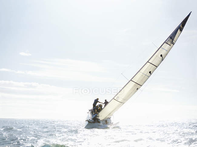 Scenic view of sailboat tilting on sunny ocean — Stock Photo