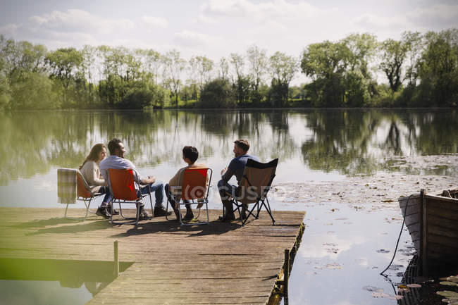 Friends talking hanging out at sunny lakeside dock — Stock Photo