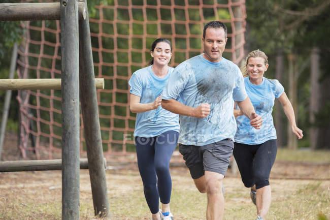 Équipe en cours d'exécution sur le parcours obstacle du camp d'entraînement — Photo de stock