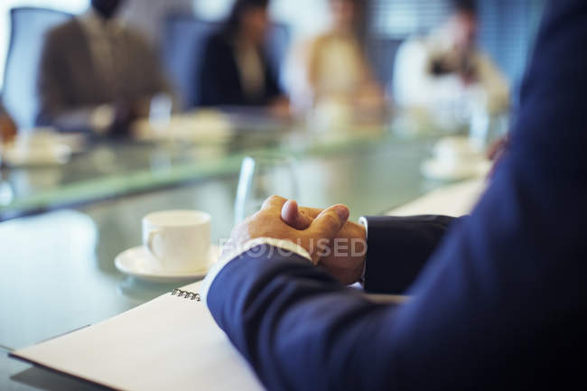 Businessman sitting at conference table in conference room with hands clasped — Stock Photo