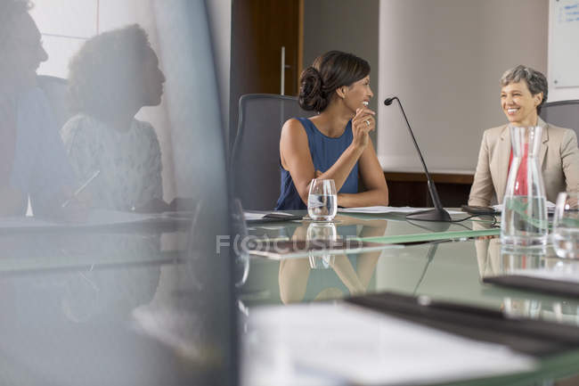 Three businesswomen sitting and talking at conference table — Stock Photo