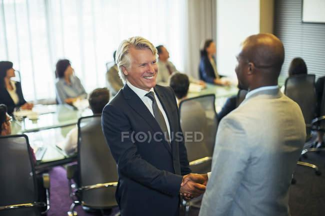 Uomini d'affari sorridenti che agitano le mani durante la riunione nella sala conferenze — Foto stock