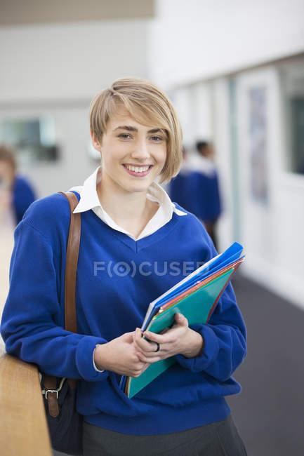 Portrait of smiling female student wearing school uniform standing in corridor — Stock Photo
